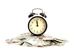Time is money concept with close up of an old clock on dollar bills. Time is money concept with close up of an old clock on a pile of dollar bills Royalty Free Stock Image
