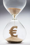 Time is money. Concept with falling sand taking the shape of a euro Royalty Free Stock Images