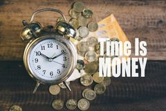 Time is money concept - golden alarm bell clock. Time is money concept - Golden bell clock,money and coins on a wooden table background with `time is Gold` word Royalty Free Stock Photo