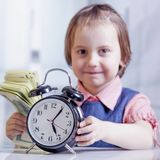 Time is money concept. Humorous portrait of cute little business. Child girl holding a clock and US Dollars in office Royalty Free Stock Images