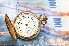 Time is money. Concept with hundred swiss franc bills and golden pocket watch Royalty Free Stock Photography
