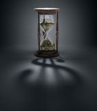 Time is money concept illustration. An hourglass casting a shadow of a dollar sign - time is money concept Stock Photos