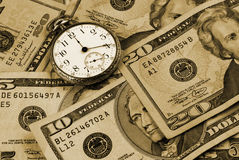 Time And Money Concept Image. Photo with crisply focused US currency and an old pocketwatch Royalty Free Stock Photo