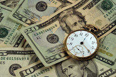 Time And Money Concept Image. Photo with crisply focused US currency and an old pocketwatch stock image
