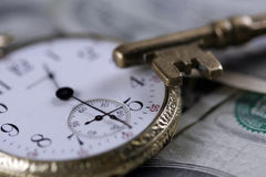 Time And Money Concept Image. Time and money portrayal by skeleton key and old pocket watch stock photo