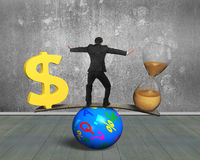 Time is money concept. Man standing between hourglass and golden dollar sign, balancing on seesaw of wood board and colorful ball, with concrete wall and wooden Royalty Free Stock Photos