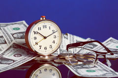 Time is money concept with old vintage clock, dollar bills, spectacles and nice reflection on blue background Royalty Free Stock Photo