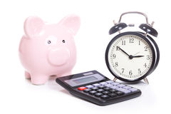 Time is money concept. With pink piggy bank, classic black alarm clock and simple old calculator, viewed from the front isolated on white background Royalty Free Stock Photos