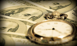 Time and money concept - pocket watch US currency Stock Photos