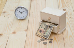 Time and money concept. Wood box with money and clock on wooden floor Royalty Free Stock Photo