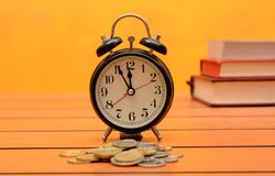 Time is money conceptual photo with clock and coins Royalty Free Stock Photo