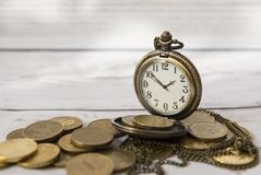 Time and money, dial, hands, pocket watch on a large variety of. Coins, vintage watches Royalty Free Stock Images