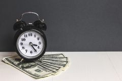 Time and money. Dollars cash. Retro alarm clock and cash money on table.