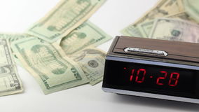 Time is Money. A fast moving red numbered on black digital clock with a variety of dollar amounts paper American money falling behind and to the side of it on a stock video footage