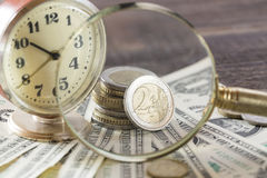 Time is money finance concept with old vintage clocks, dollar bills, magnifying glass and euro coins Stock Photos