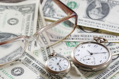 Time is money finance concept with old vintage clocks, dollar bills, spectacles Stock Photo