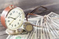 Time is money finance concept with old vintage clocks, dollar bills, spectacles and euro coins Royalty Free Stock Image