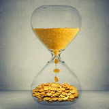 Time is money financial opportunity concep. T. Sand clock with gold dust and coins  on gray wall background Stock Photo