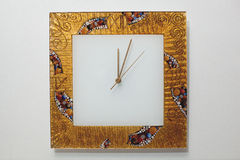 Time is money. Gold square wall clock with shooters Stock Image