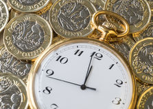 Time and money, a gold watch on top UK pound coins Stock Photo