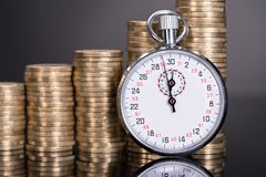 Time and money growth. Over black background Royalty Free Stock Photos
