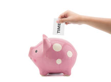 Time and money - hand putting a clock into a pink piggy bank Royalty Free Stock Photos