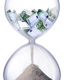 Time is money. Hourglass filled with bills of one hundred euros. Symbolizes time business processes Royalty Free Stock Images