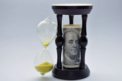 Time is money. Hourglass with US currency on white backgraund Stock Photo