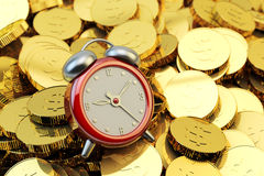 Time is money, make money, finance and business concept. Red alarm clock at the heap of gold coins closeup view Stock Photo