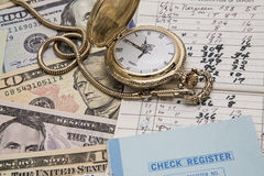 Time money management checkbook concept. The hand written check book register from the bank account is used to balance the money deposits with time and money stock image