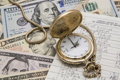 Time money management pocket watch checkbook. The concept of time and money management is shown with the ancient pocket watch and cash paper bills lying under stock images