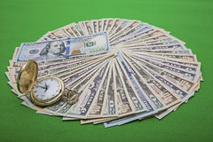 Time money management USA bills watch. The circular fanned pile of United States paper currency bills and gold plated pocket watch displays a time money concept Royalty Free Stock Photo