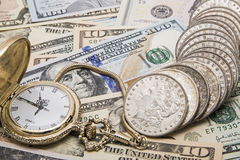 Time money management watch silver dollars savings. Time and money management concept includes old American silver morgan dollar coins and new paper currency Royalty Free Stock Photography