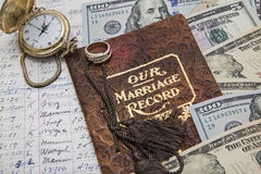 Time and money in marriage. The expense listing and marriage record book with the golden pocket watch and wedding band shows the concept of working together over Royalty Free Stock Photo