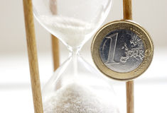 Time is money one euro coin. One Euro coin stuck on sandglass corps Royalty Free Stock Photos