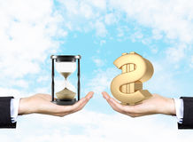 Time is money. One hand holding sand glass, another golden dollar sign. Blue sky at background. Concept of time is money Stock Images