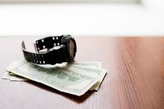 Time is money. One hundred dollars and black watch on wooden table royalty free stock photos