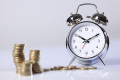 Time is money silver clock and gold pound coins Royalty Free Stock Images