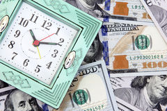 Time is money. 100 usd american dollar bills with old clock to mean time is money Stock Images