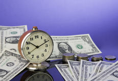 Time is money, vintage clock on cash american dollar bills and coins with nice blue background. Business Commerce concept Royalty Free Stock Photography