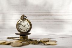 Time and money, vintage clock, pocket watch  on a pile of coins. Watch face, hands Stock Photography