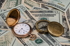 Time money watch and compass. Investing for retirement and future plans. This conceptual photo illustrates, savings, direction, retirement and financial planning Royalty Free Stock Photo
