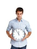 Time is money - Young man holding a clock in hand Royalty Free Stock Images