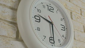 Time nine hours thirty minutes. Timelapse. Round white clock hanging on brick wall. stock video footage