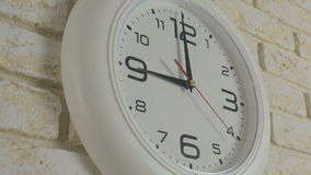 Time nine hours. Timelapse. Round white clock hanging on brick wall. Time nine hours. Timelapse. Round white clock hanging on a brick wall stock footage