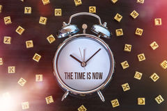 The time is now. Alarm clock on wooden table with letters stock photos