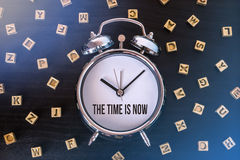 The time is now. Alarm clock on wooden table with letters royalty free stock photography