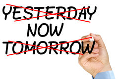 Time is now. Businessman hand crossing tomorrow yesterday words versus now with marker on clear glass whiteboard isolated Stock Photo