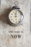 The time is now concept. The time is now, vintage alarm clock on a brown background Royalty Free Stock Images