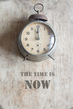 The time is now concept. The time is now, vintage alarm clock on a brown background Royalty Free Stock Photography